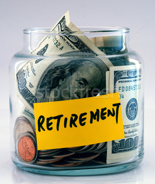 "Stock photo: A lot of money in a glass bottle labeled ""Retirement"""