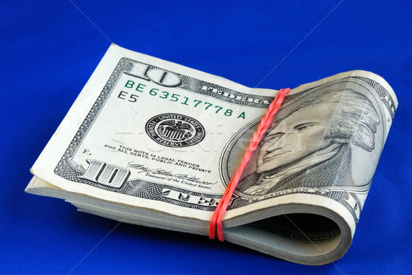 A strap of ten dollar bills isolated on blue Stock photo © johnkwan