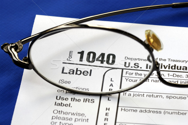 Focus on the United States Income Tax 1040, isolated on blue background Stock photo © johnkwan