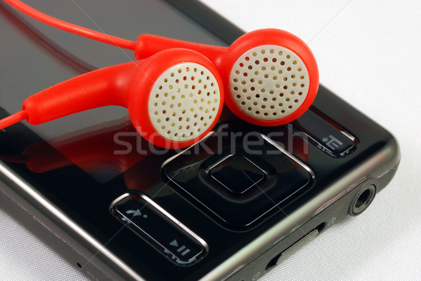 Red earphones on a MP3 player concepts of music download and piracy Stock photo © johnkwan