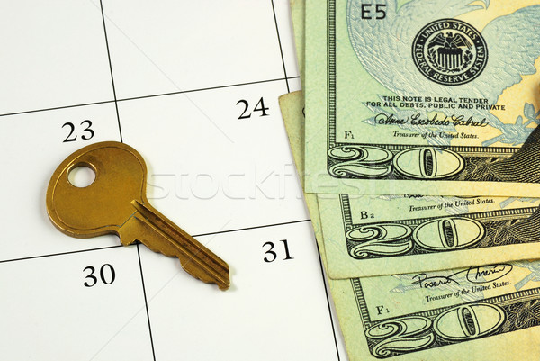 Stock photo: Key and money on a calendar concepts of paying the mortgage on time