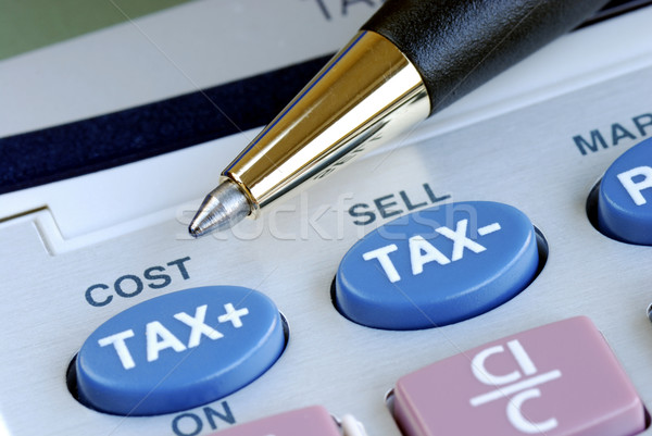 Stock photo: Calculate the tax and the cost with a calculator
