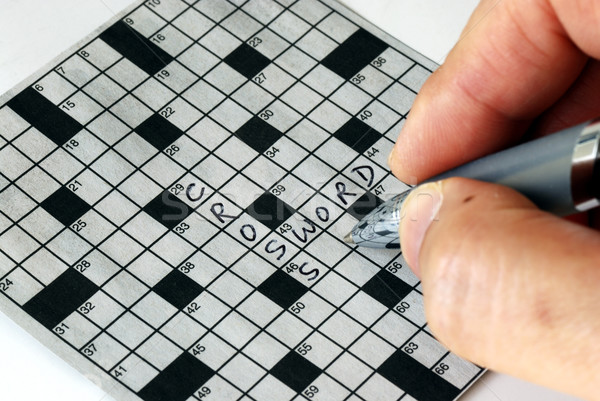 Solving the cross word puzzle from the newspaper Stock photo © johnkwan