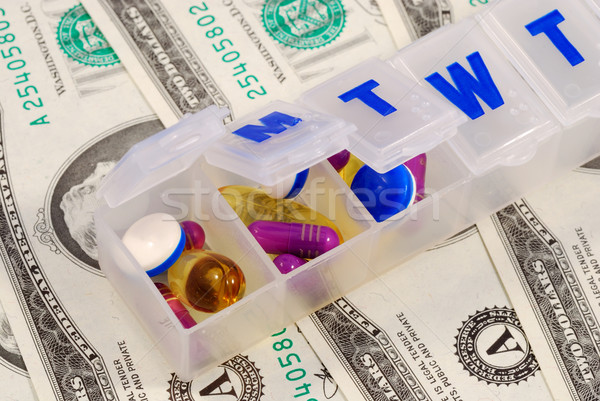 Drug holders on some dollar bills concepts of rising medical cost Stock photo © johnkwan