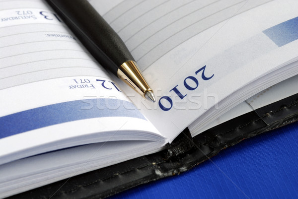 Close up view of the diary with a pen isolated on blue Stock photo © johnkwan