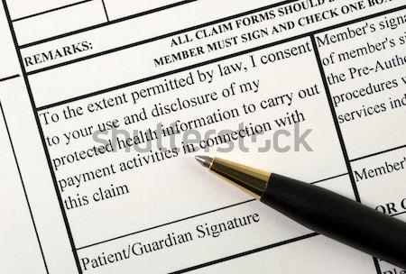 Filling the health insurance claim form with a pen Stock photo © johnkwan