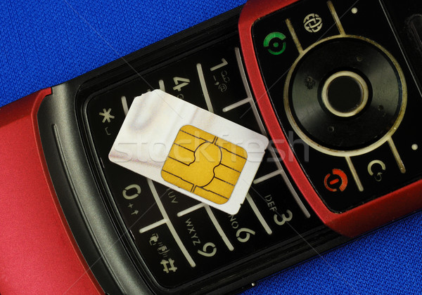 Cellular phone with a SIM card isolated on blue concepts of wireless communication Stock photo © johnkwan