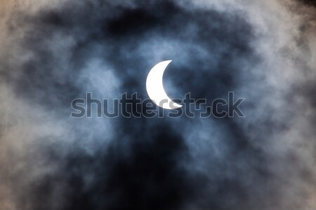 Partial solar eclipse through clouds Stock photo © Juhku