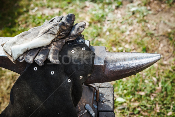 Worn iron anvil apron and gloves Stock photo © Juhku