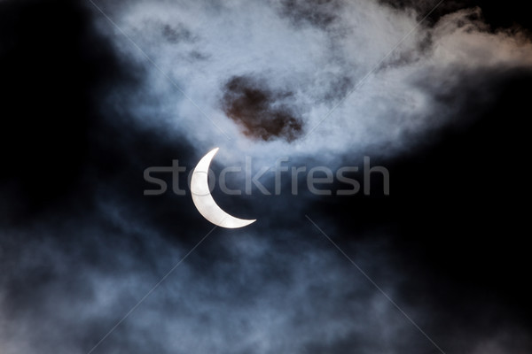 Partial solar eclipse through clouds Stock photo © Juhku