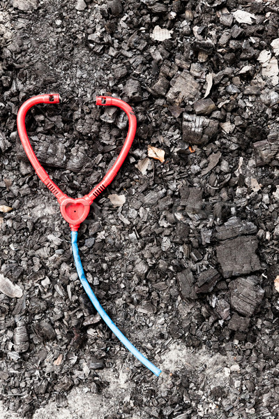 Plastic toy stethoscope on burned ground Stock photo © Juhku