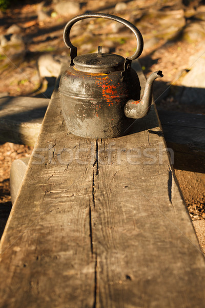 Stock photo: Old kettle in wooden bench outdoors