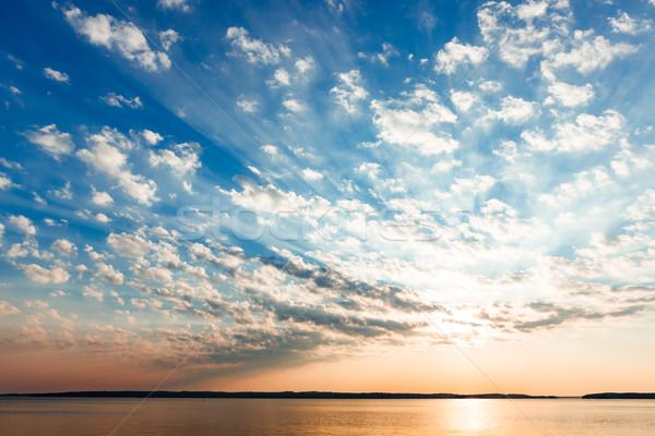 Clouds and sun rays over lake at sunrise Stock photo © Juhku