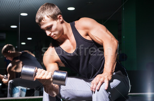 Portrait of handsome muscular man doing concentration curls on bench Stock photo © julenochek