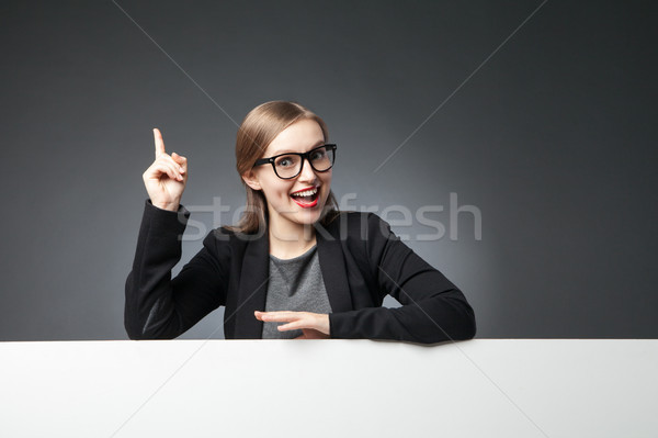 Woman in glasses and jacket with index finger up Stock photo © julenochek