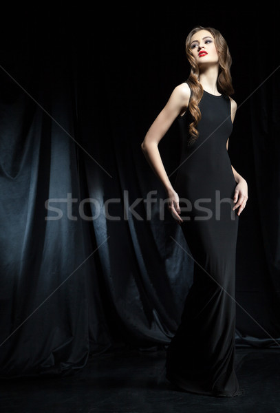 Elegant woman in black dress with arms on hips Stock photo © julenochek