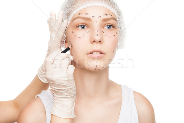 Hands in gloves painting outlines on girl's face Stock photo © julenochek