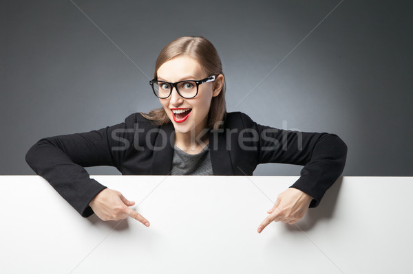 Happy woman with open mouth pointing at blank space Stock photo © julenochek