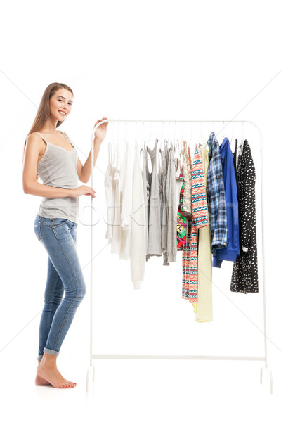 Side view of beautiful young brunette near clothes hanger Stock photo © julenochek