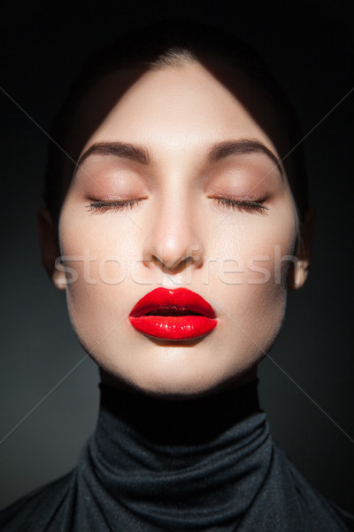 Stock photo: Attractive young model with red lips and forehead in shadow