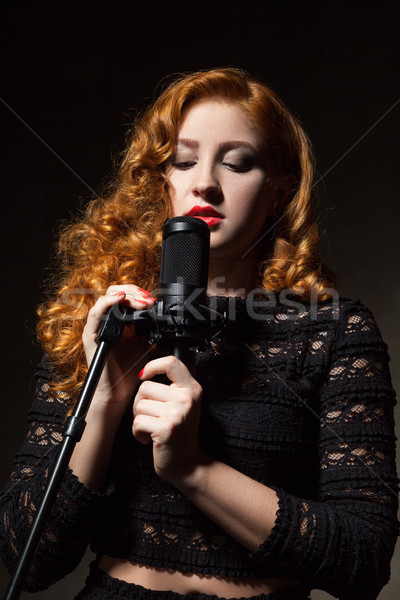 Stock photo: Portrait of curly-haired singer with red lips holding mic