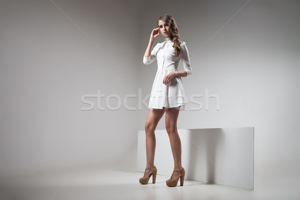 Stock photo: Girl in white dress posing against of grey