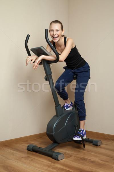 Cheerful teen girl cycling on home bike Stock photo © julenochek