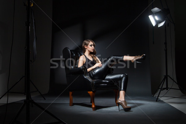 Model in spotlight posing on black leather chair in studio Stock photo © julenochek