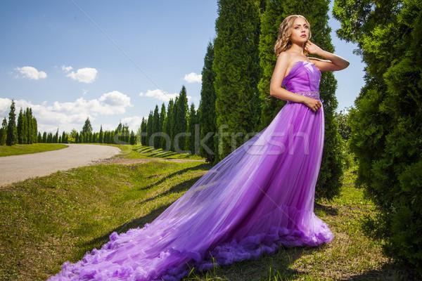 Elegant woman in violet long dress against of green alley Stock photo © julenochek