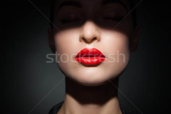 Stock photo: Beautiful model with bright red lips and face half covered in shadow