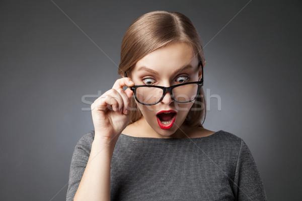 Wide-eyed woman in glasses looking down in amazement Stock photo © julenochek