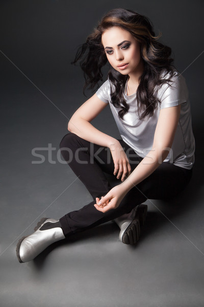Portrait of young woman with windy hair sitting on floor in studio Stock photo © julenochek