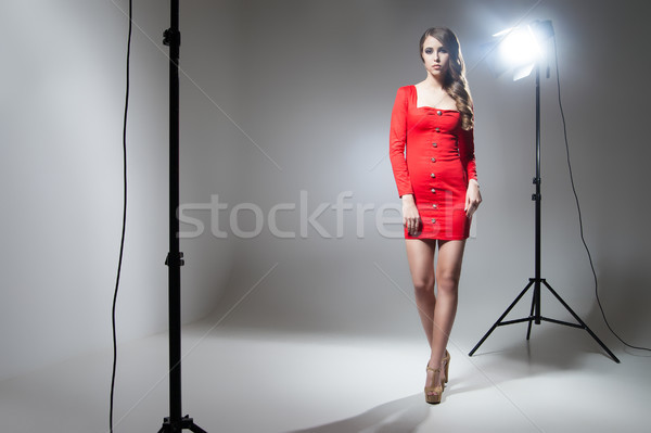Young model in red dress posing in spotlight Stock photo © julenochek