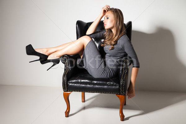Portrait of long-haired girl on leather chair Stock photo © julenochek