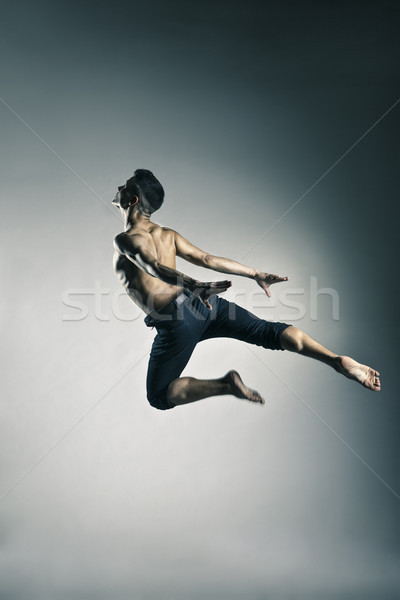 Caucasian man gymnastic leap posture on grey Stock photo © julenochek