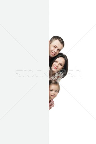 Famiglia felice nascondere dietro cartellone ritratto bianco Foto d'archivio © julenochek