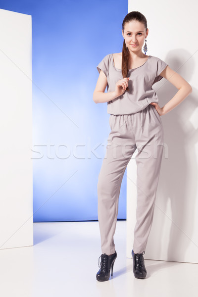 Stylish woman in overall looking at camera Stock photo © julenochek