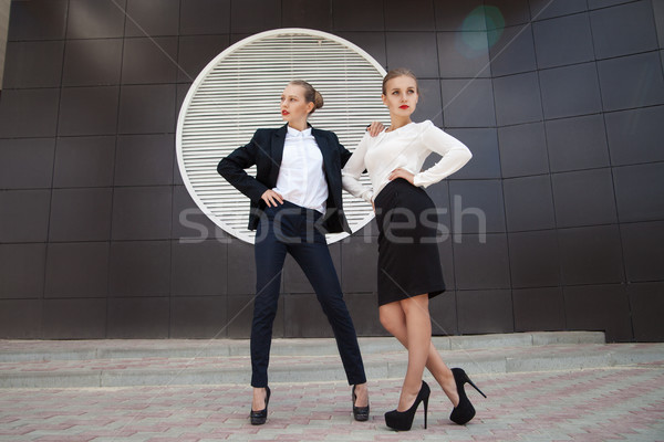 Stock photo: Two stylish women posing against of building wall