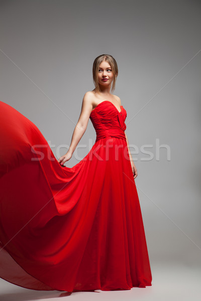 Beautiful model in red dress with flying skirt