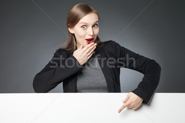 Astonished woman with red lips pointing at blank space Stock photo © julenochek