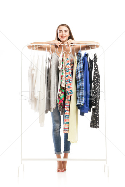 Portrait of smiling brunette behind hanger with clothes Stock photo © julenochek
