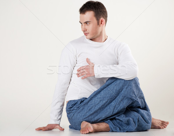 healthy young man doing yoga. Spine twisting pose Stock photo © julenochek