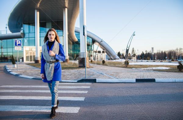 Side view of brunette in blue coat going on crosswalk Stock photo © julenochek
