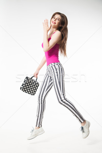 Brunette model jumping with leg up and holding polka dot bag Stock photo © julenochek