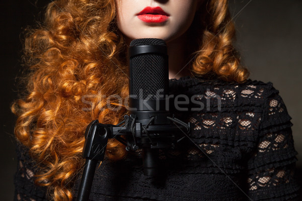 Stock photo: Close-up of curly-haired woman with mic