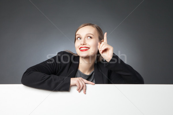 Smiling businesswoman with finger up Stock photo © julenochek