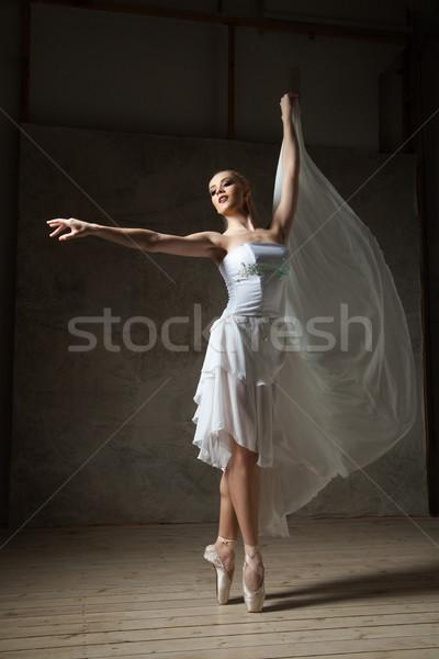 Elegant ballerina dancing in white costume and ballet shoes Stock photo © julenochek