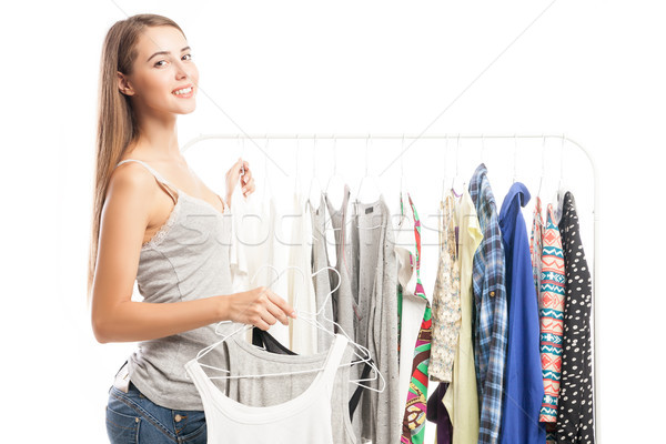 Side view of young beautiful girl with tops on hangers in hand Stock photo © julenochek