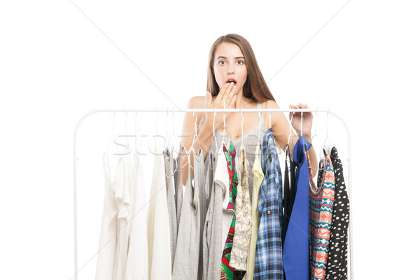 Brunette covering mouth in surprise near hanger with clothes Stock photo © julenochek