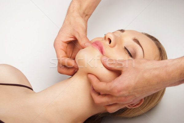 Stock photo: Young woman receiving a head massage on white